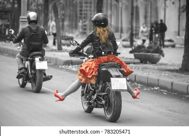 photo of a girl in a red skirt and red shoes. a girl on a motorcycle