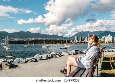 Photo of Girl Sitting on a Bench at Kitsilano Beach in Vancouver, Canada