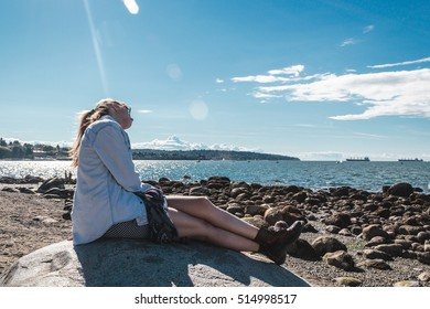 Photo of Girl Sitting on a Rock at Kitsilano Beach in Vancouver, Canada