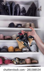 Photo of girl taking a pair of high heels in with shoes on shelves in the background