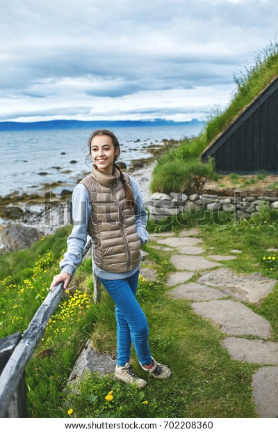 photo of girl in warm clothing posing on pier with background of mountains and ocean of West Fjords, Iceland.