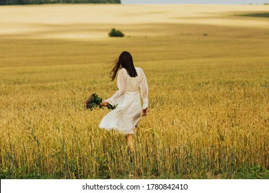 Photo of the girl's back in the wheat field. Happy woman walks in wheat. Free woman. Gorgeous woman holding a bouquet of flowers in his hand.