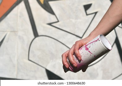 Photo of a girl's hand with aerosol paint cans in hands on a graffiti wall background. The concept of street art and use of aerosol paints. Graffiti art shop background image