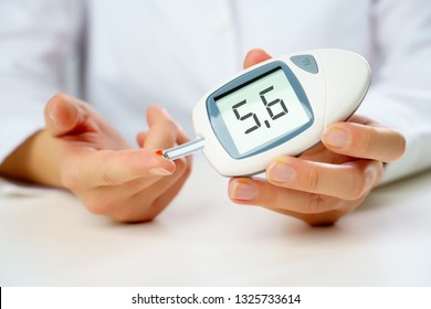 Photo of girl's hand with glucometer.