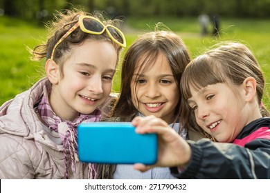 Photo of girls making selfie in the park