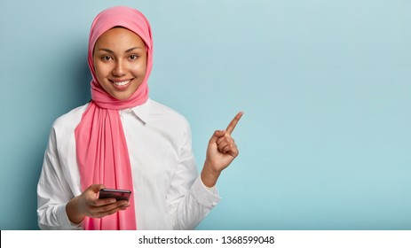 Photo of glad Arabic woman with gentle smile on face, points with fore finger on blank space, pink veil on head, holds mobile phone for texting messages, isolated against blue wall, browses internet