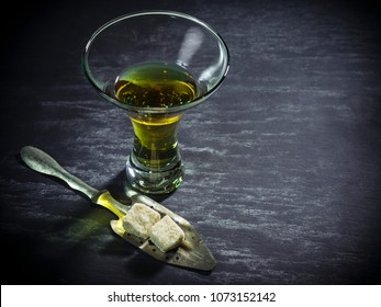 Photo of a glass of absinthe with spoon and sugar cubes.