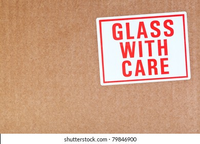 Photo of a Glass with care sticker on a cardboard background.