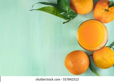 A photo of a glass of citrus juice with vibrant orange tangerines with green leaves, shot from above on a light background texture with copy space. Selective focus