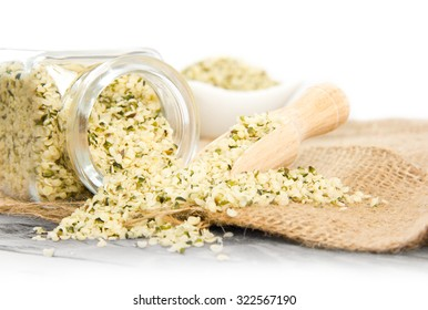 Photo of glass spicebox full of chia seeds on burlap with white space