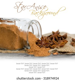 Photo of glass spicebox full of ground star anise spice on burlap with white space