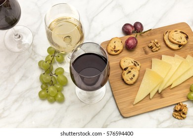 A photo of glasses of white and red wine at a tasting, with cheese, bread, and grapes