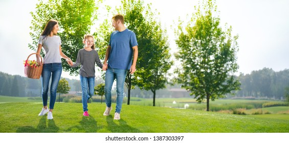 Photo of going on picnic happy family, countryside or park. Happy childhood and summertime concept image. Copy space empty place for some text, advertising or slogan. Sunny day picture.