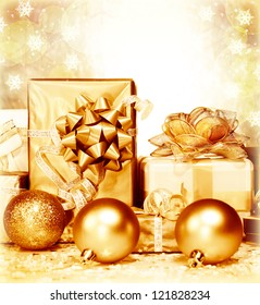 Photo of golden Christmas presents on blur background, different gift box wrapping in shiny paper and decorated with ribbon bow, New Year surprise, happy holiday, Xmas ornament, festive greeting card