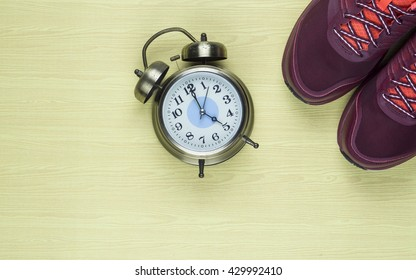Photo of the golden clock and sport shoes on the wooden background.Fitness with running at five o'clock.Top view sport equipment. Selective focus.
