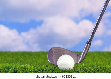 Photo of a golf iron club behind the ball on the fairway.
