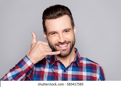 """A photo of good-looking young man in checkered shirt isolated on gray background making a gesture """"call me"""" with his fingers"""