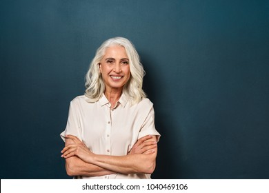 Photo of gorgeous mature old woman standing isolated over dark blue background wall looking camera with arms crossed.