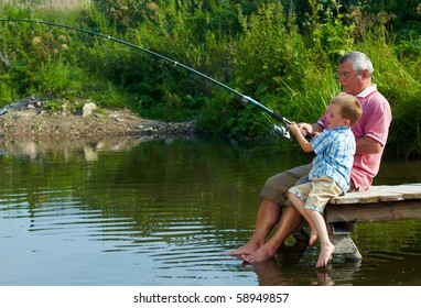 Photo of grandfather and grandson sitting on pontoon with their feet in water and fishing on weekend