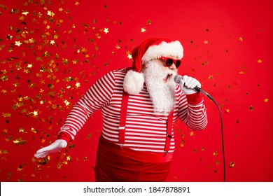 Photo of grandpa grey beard hold mic open mouth scream sing song karaoke wear santa claus x-mas costume suspenders sunglass striped shirt cap isolated red color background