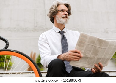 Photo of gray-haired bearded businessman in eyeglasses reading newspaper while sitting on bench with bicycle outdoors