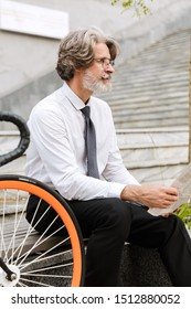 Photo of gray-haired confident businessman in eyeglasses reading newspaper while sitting on bench with bicycle outdoors