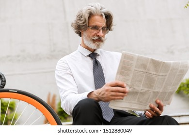 Photo of gray-haired elderly businessman in eyeglasses reading newspaper while sitting with bicycle outdoors