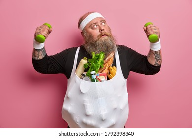 Photo of greedy fat man looks above surprisingly, raises dumbbells, poses with products goes in for sport, being crazy food lover tries to lose weight and be fit. Healthy lifestyle and fitness concept