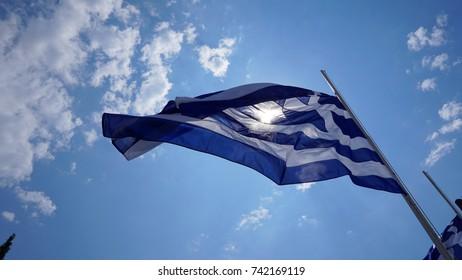 Photo of Greek flag waving in a little cloudy blue sky