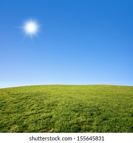 Photo of a green grass field with deep blue sky on a sunny day