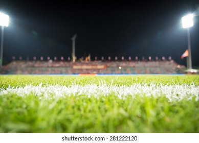 Photo of a green synthetic grass sports field with white line shot.Green grass in soccer stadium: Soccer ball on soccer field. Soccer or football ball symbol on the green field. Soccer ball on field.