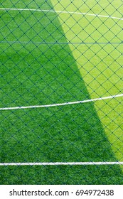Photo of a green synthetic grass sports field with white line shot from above