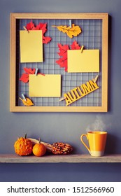 """Photo grid board with red and orange paper Autumn leaves and text """"Autumn"""". Autumn decorations and orange cup on a shelf below the iron grid. Fall-related mockup for your photos, cards or lettering on"""