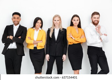 Photo of a group of concentrated colleagues standing in office posing. Looking at camera.