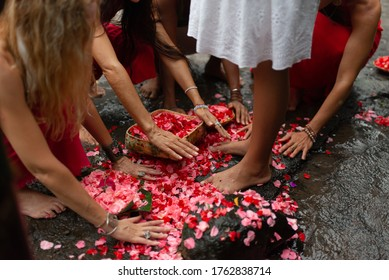 photo of a group of girls worshiping at the feet of a girl with hands sticks of red flowers that fell to the ground