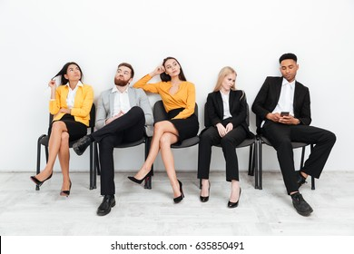 Photo of a group of tired colleagues sitting in office while looking aside.