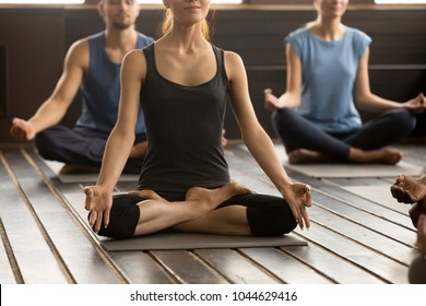 Photo of group of young sporty people practicing yoga lesson, sitting in Sukhasana exercise, Easy Seat pose, working out, students training in sport club, studio close up view
