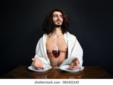 photo guy with long curly hair white drapery and two empty plates and with glass of red wine looking up