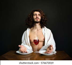photo half naked handsome guy with long curly hair at the table with two white empty plates and a glass of red wine is praying