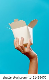 Photo of hand with cardboard box for wok isolated