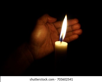Photo of hand covering flame of candle from wind
