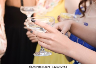 Photo of the hand of a girl with a glass of champagne at a party