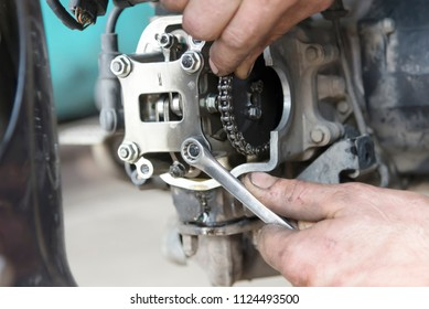 Photo of hand holding the key, repairing the motorcycle engine in the garage, close-up