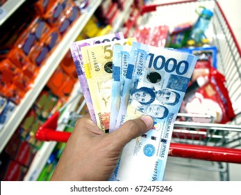 Photo of a hand holding Philippine Peso bills while inside a grocery store