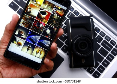 Photo of a hand holding a smartphone over a digital mirrorless camera and laptop computer