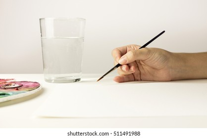A photo of a hand holding a watercolor brush, with a water glass for cleaning it, and a blank sheet of paper with plenty of copyspace