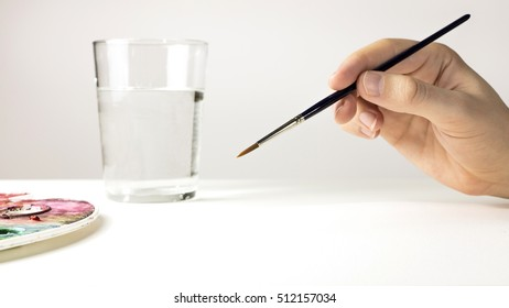 A photo of a hand holding a watercolor brush, with a palette, a water glass on the blurred background, and a blank sheet of paper with plenty of copyspace