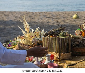 A photo of a hand performing a Hindu religious ritual possession which is held on Berawa Beach, Bali in the morning