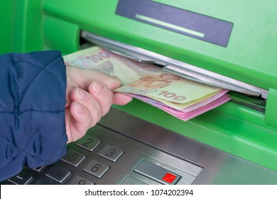 Photo of the hand taking from ATM Ukrainian hryvnas