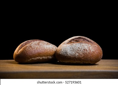 photo of handmade black bread on black background. Black bread on wooden table close-up.